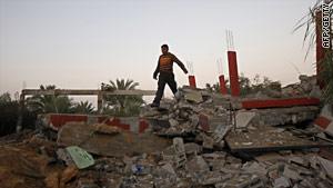 A Palestinian man inspects damage following Israeli air raids in Deir al-Balah, Gaza, on November 19, 2010.