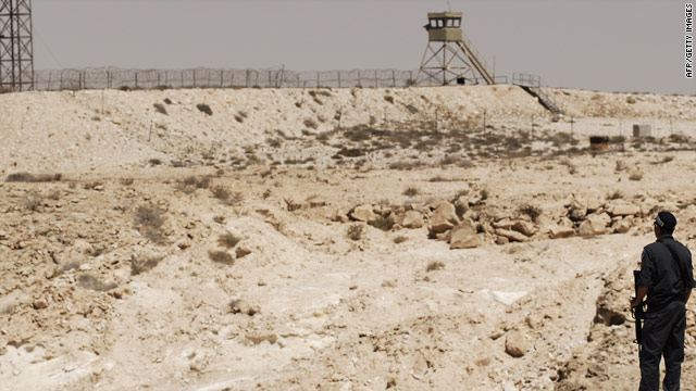 An Israeli policeman looks across to the Egyptian border from his own side.