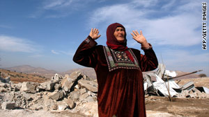 A woman reacts to the rubble of a mosque in the West Bank village of Khirbet Yarza.