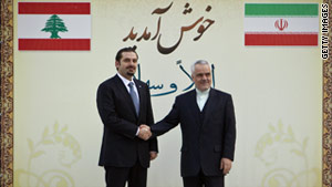 Lebanese Prime Minister Saad Hariri, left, shakes hands with Iran's first vice president, Mohammad Reza Rahimi.
