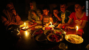 A Gaza family eats during an outage in August. A report says the easing of a blockade hasn't helped much.