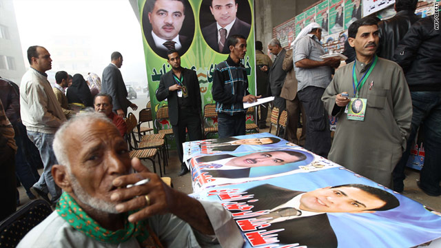 Egyptians gather in the Bulak al-Dakrur district of Cairo filled with campaign posters on December 5.