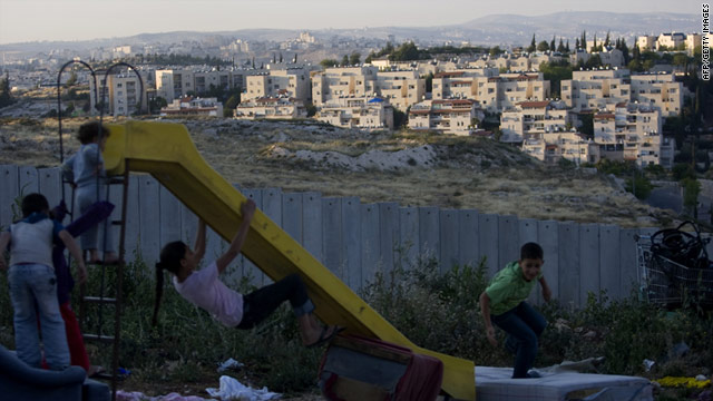 Palestinian children play on one side of a barrier wall; on the other is the Pisgat Ze'ev neighborhood of East Jerusalem.