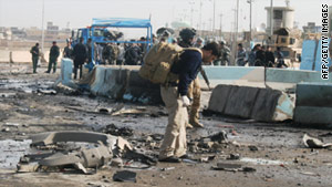 Iraqi security forces survey the scene of a suicide attack in Ramadi,