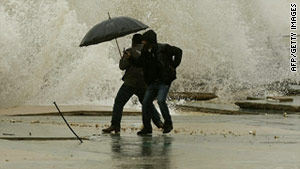 Two Lebanese men face the onslaught as waves crash into a promenade in the southern city of Sidon on Sunday.