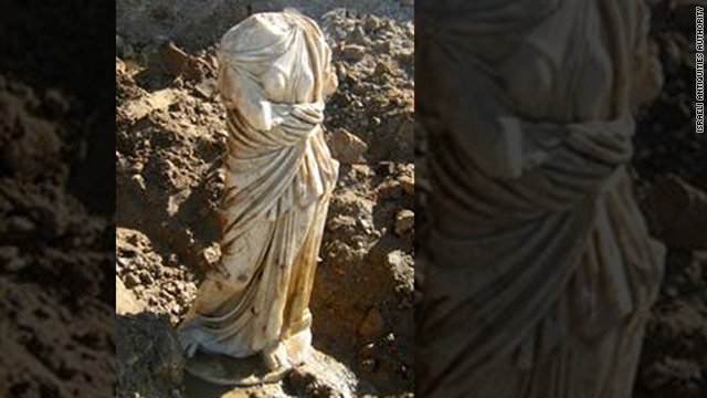 The white marble statue of a woman wearing a toga and sandals has no head or arms.