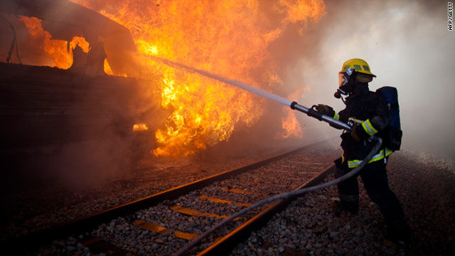 An Israeli fire fighter tackles a blaze after a train caught fire on December 28, 2010 in Bnei Zion, Israel.