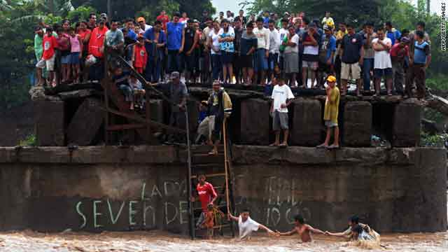 People try to cross the overflowed Huiza River, as others look from a damaged bridge in La Libertad, El Salvador.