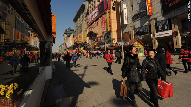Shoppers walk through a busy retail street in Beijing as China overtakes Japan in terms of GDP.
