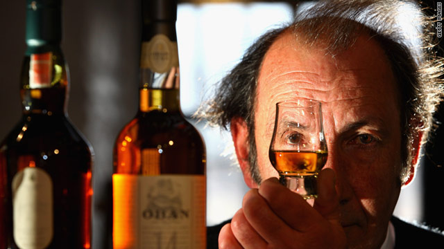 An employee at Diageo's Dalwhinnie distillery inspects a sample of whisky in the visitor centre in Scotland.