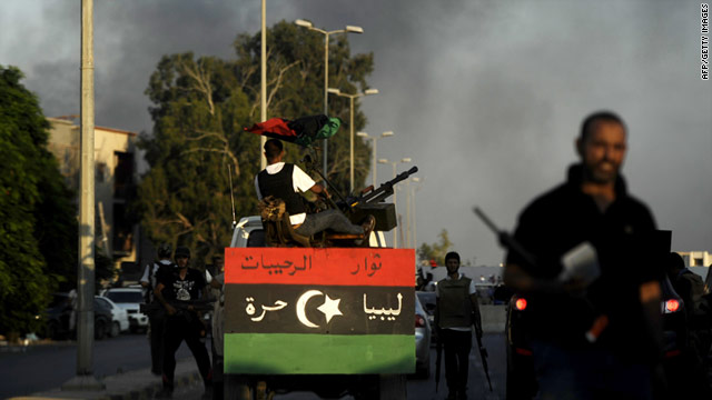 Smoke billows in the background as Libyan rebels overrun Moammer Gadhafi's fortified Bab al-Azizya headquarters in Tripoli
