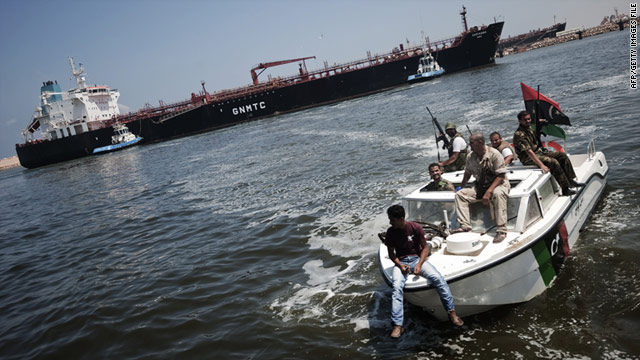 Small boats of Libyan rebels escort an oil tanker, laden with 73,000 tons of petrol, as it docks in the Benghazi harbor on August 5.