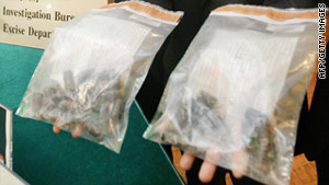 The head of Hong Kong Customs' Drug Investigation Bureau displays bags of cocaine following a bust in 2006.