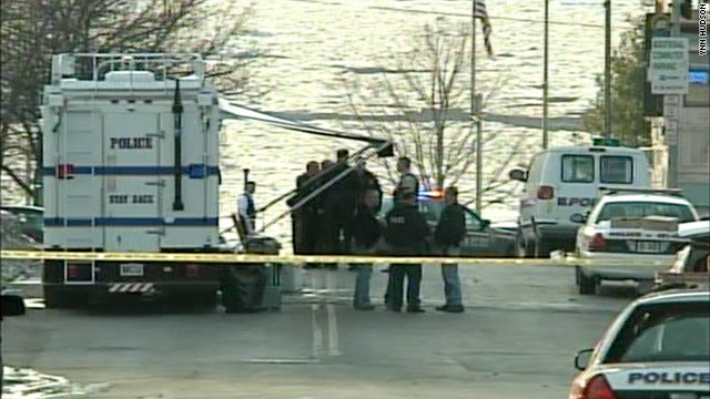 Police in Poughkeepsie, New York, investigate the scene where a police officer and two other people were shot.