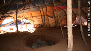Participants engaged in a rebirthing ritual in a sweat lodge made of branches and tarps.