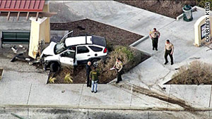 The suspect's vehicle crashes into a building Tuesday in Palmdale, California, with deputies in pursuit.