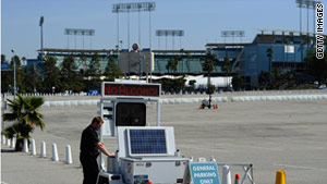 A Los Angeles police officer installs license plate and speed monitoring equipment outside Dodger Stadium on Thursday.