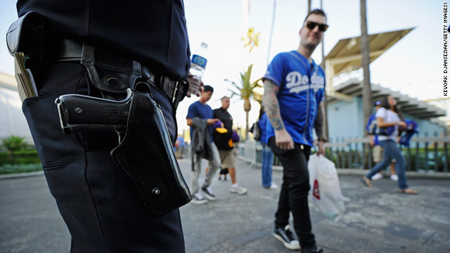 A Los Angeles Police officer stands watch as fans arrive at Dodger Stadium prior to the start of the Dodgers game.
