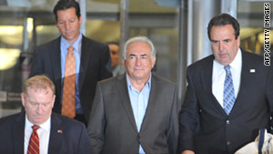 Former IMF head Dominique Strauss-Kahn leaves a New York building under guard on Wednesday.
