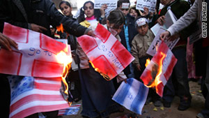 Protesters burn the Danish flag. Tahawwur Hussain Rana was found guilty of aiding a plot against a Danish paper.