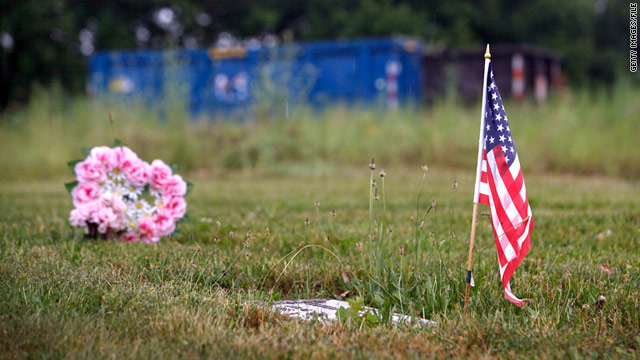A flag marks a grave at Burr Oak Cemetery in Alsip, Illinois. A pile of human remains was found behind the blue dumpster in the background in 2009.