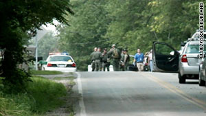 Law enforcement officers investigate Sunday after a gunman shot to death seven people in Copley Township, Ohio.