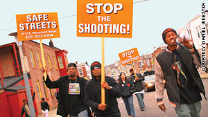 Tard Carter, right, leads a rally after a shooting in Baltimore.