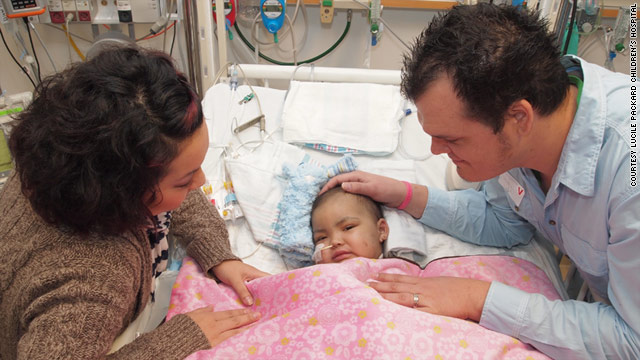 Ryan and Leah Jeffers lean over their daughter Malyia in the hospital.
