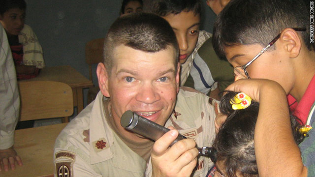 Mike Moore, seen here in Tikrit with children from Iraq, decided in his mid-40s to go to medical school.