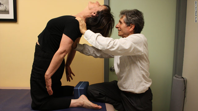 Dr. Loren Fishman shows Dr. Carolyn LaFleur the camel pose to help get rid of her headaches.