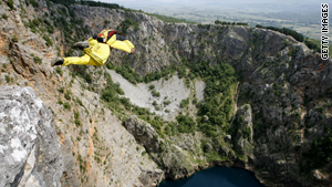 BASE jumper leaps from a cliff to land into the Red Lake near Croatian town of Imotski.