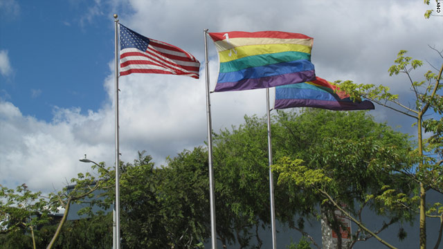 The American flag and the gay pride rainbow flag fly side by side in West Hollywood, California.