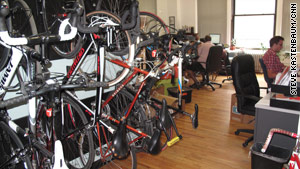 Bikes line the wall of an office with bicycling commuters.