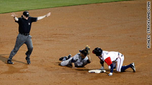Umpire Mike Estabrook declares Gwinnett Braves center fielder Jordan Schafer, right, safe at second base.