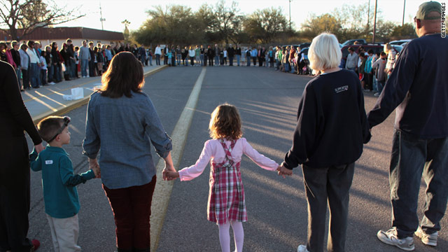 Rachel Crabb, 5, holds hands with teachers and parents during moment of silence for her schoolmate Christina Green in Tucson.