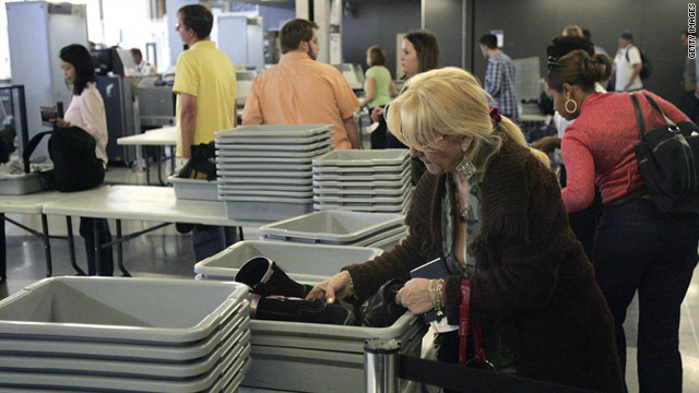 An air traveler places some of her belongings into a bin at a security checkpoint at O'Hare International Airport in Chicago.