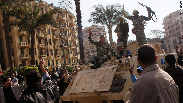 Egyptian soldiers drive an armored personel carrier slowly through a crowd of protesters in Cairo's Tahrir Square on Sunday.