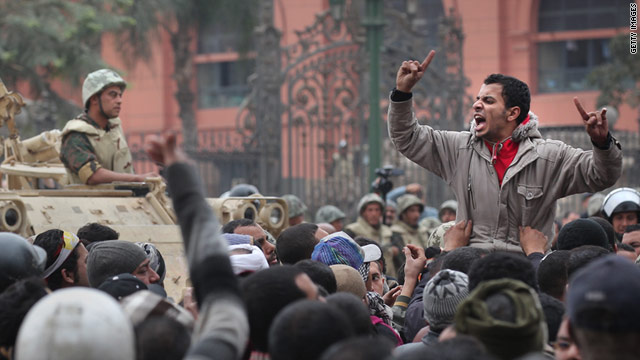 An anti-government protester chants and gestures in front of soldiers guarding the Egyptian Museum in Tahrir Square.