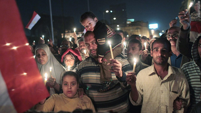 Anti-government protesters walk in Tahrir Square during a candlelight vigil for those killed during the uprising.