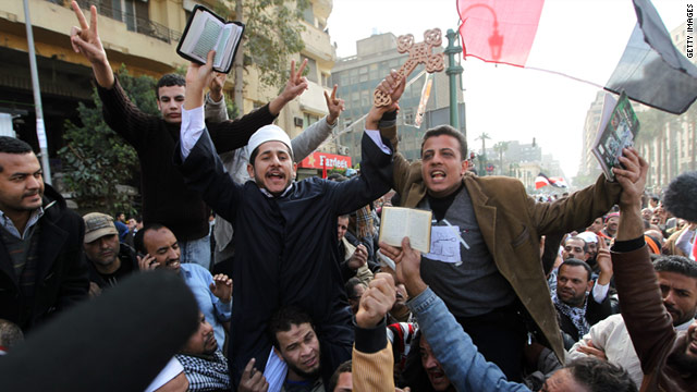 Coptic Christians and Muslims raise a Cross and a Koran at Cairo's Tahrir Square on February 6.