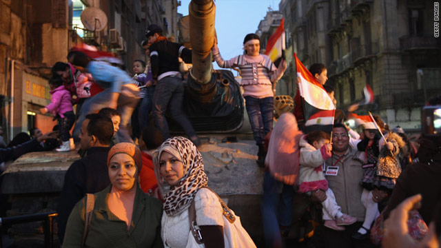 Egyptians pose for photos atop and around an Egyptian army tank on Sunday in Cairo.