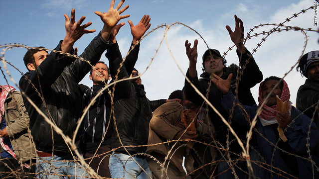 Men reach for bread while waiting to enter Tunisia last week after fleeing Libya.