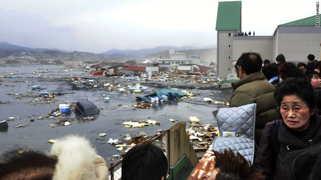 Residents survey the devastation from a tsunami wave  at Kesennuma city in Miyagi prefecture, northern Japan.