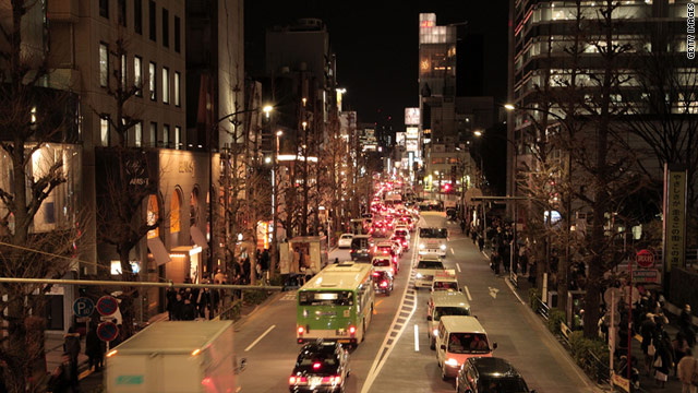 Pedestrians and cars make their way in Tokyo after train services are suspended following the earthquake.
