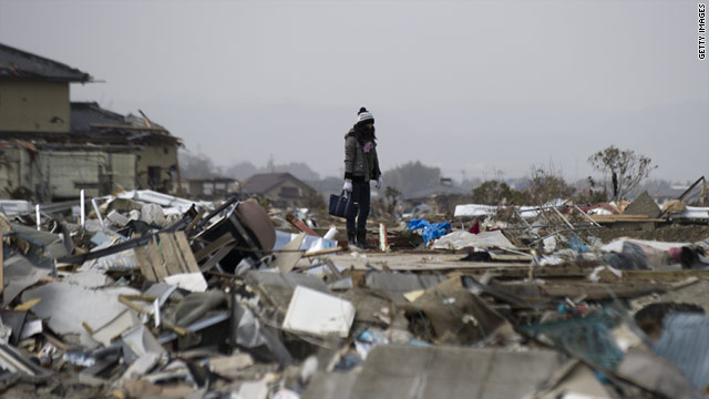 A woman stands on debris in Natori, Miyagi Prefecture, after the 9.0 earthquake and tsunami in Japan.