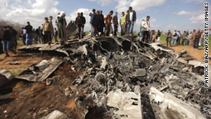 People gather at the wreckage of a U.S. F-15 fighter jet, southeast of Benghazi, Libya, on March 22, 2011.