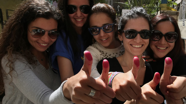 Egyptian women show their ink-stained thumbs in Cairo on Saturday after voting on a package of constitutional changes.