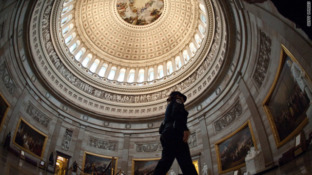 A Capitol policewoman walks through the empty Rotunda.