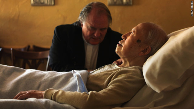 A chaplain prays with a resident in the Hospice of Saint John  in Colorado, which accepts people regardless of their ability to pay.