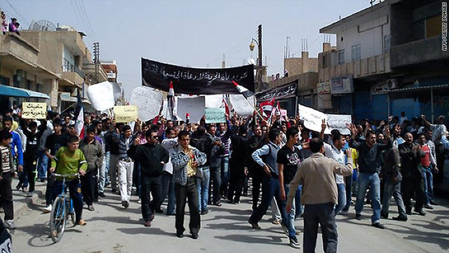 Syrian anti-government protesters march in the northeastern town of Qamishli on Friday, April 1.